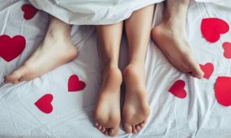 Füße von Paar beim Sex im Bett mit roten Herzen