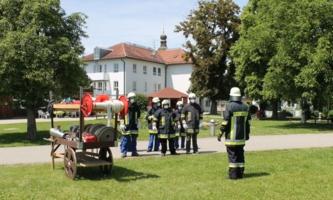 Feuerwehrleute haben sich auf Wiese aufgestellt