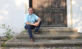 Alfred Roßmadl auf Treppe vor alter Holztür