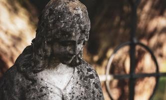 Statue auf Grab mit Kreuz