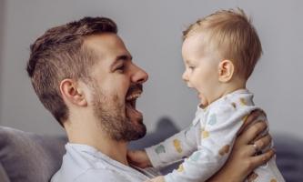 Vater und Baby lachen sich an und sagen Ah