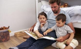 Vater und zwei Kinder schauen Bilderbuch an