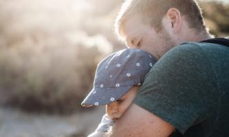 Vater hält Kleinkind liebevoll im Arm