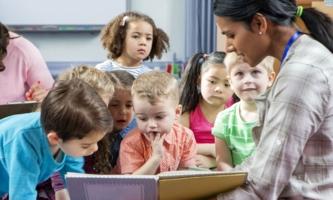 Kindergartenkinder lesen in Buch mit Erzieherin