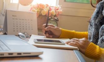 Hände von Frau mit Notebook, Handy und Tischkalender
