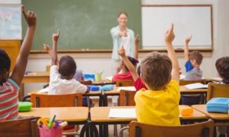 Schülerinnen und Schüler im Klassenzimmer melden sich