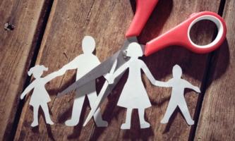 Schere zerschneidet Papierfigurenfamilie