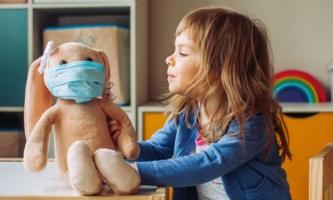 Kindergartenkind mit Stoffhase, der Mund-Nasen-Maske trägt