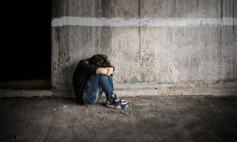 Junge Frau sitzt einsam in dunkler Straßenecke