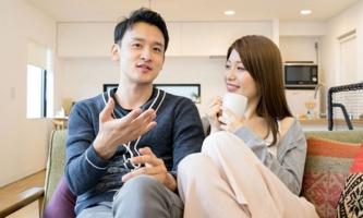 Frau und Mann sitzen auf Sofa und unterhalten sich
