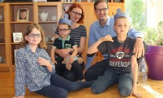 Vater und Mutter Gergen mit ihren drei Kindern im Wohnzimmer