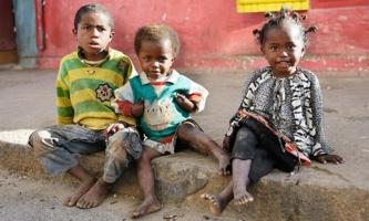 Drei Kinder sitzen auf Gehsteig in Madagaskar