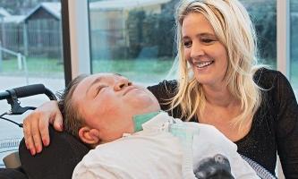 Susanne Greis mit ihrem Sohn, der mit Beatmungerät im Rollstuhl liegt