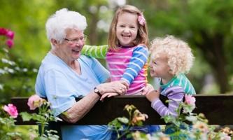 Fröhliche Oma mit Enkeltöchtern auf Gartenbank