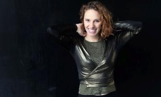Kassandra Wedel lachend vor schwarzem Hintergrund