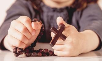 Mädchen hält Rosenkranz in den Händen