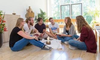 Jugendliche sprechen im Kreis auf Boden in der Kapelle des Münchner Salesianums