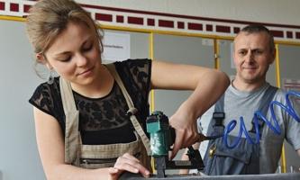 Junge Frau arbeitet mit elektrischem Gerät an Möbelstück