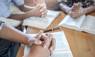 Gefaltete Hände mit Bibeln auf dem Tisch