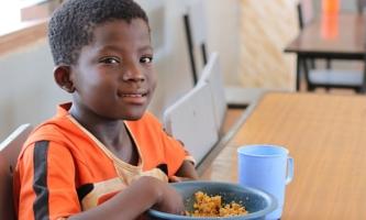 Junge sitzt bei Don Bosco in Ghana am Tisch und isst