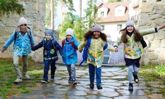 Kinder halten sich an den Händen und rennen über Gehweg