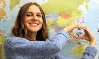 Sara Straub formt vor Weltkarte mit den Händen ein Herz