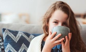 Mädchen auf Sofa mit Decke trinkt Tee