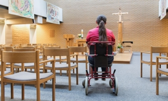 Frau im Rollstuhl in der Klinikkirche des Klinikums der Universität Großhadern in München