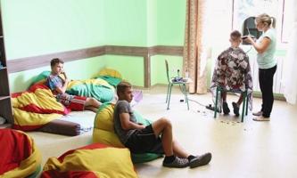 zwei Jungen liegen auf Kissen, ein dritter bekommt die Haare geschnitten