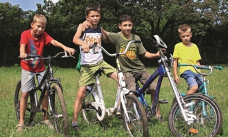 Vier Jungen mit Fahrrädern auf einer Wiese
