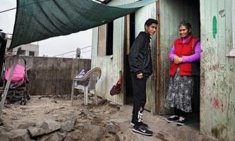 Jugendlicher mit seiner Großmutter vor einfachem Holzhaus