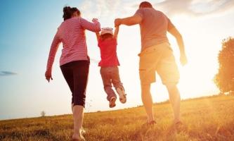 Eltern tragen Kind zwischen sich an den Händen über eine Wiese im Sonnenuntergang