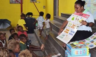 Lehrerin zeigt auf dem Boden sitzenden Kindern eine Bildtafel