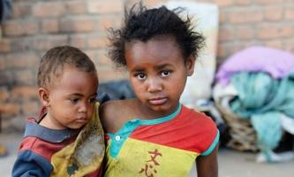 Kind trägt Kleinkind auf dem Arm auf einer Straße