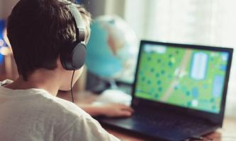 Junge mit Kopfhörern vor Computerbildschirm