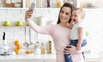 Mutter macht Selfie von sich mit Baby auf dem Arm