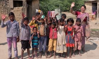 Kinder einer Schule für Musahar mit ihrer Lehrerin auf Dorfplatz in Indien