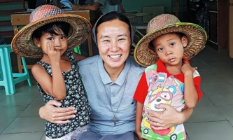 Schwester mit zwei Kindern im Kindergarten der Don Bosco Schwestern in Myanmar