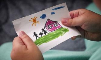 Kinderhände mit Zeichnung von Familie und Haus