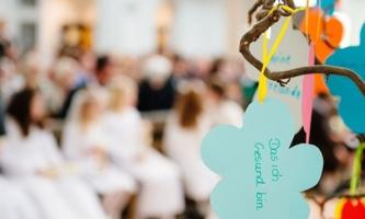 Erstkommunionkinder in Kirche, im Vordergrund beschriftete Zettel