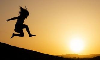 Mädchen springt im Sonnenuntergang