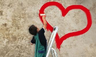 Kind malt mit roter Farbe Herz an Wand