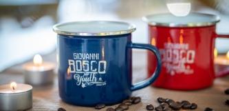 blauer und roter Emaillebecher mit Kaffeebohnen und Teelicht
