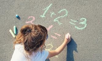 Mädchen malt mit Kreide Rechenaufgaben auf die Straße